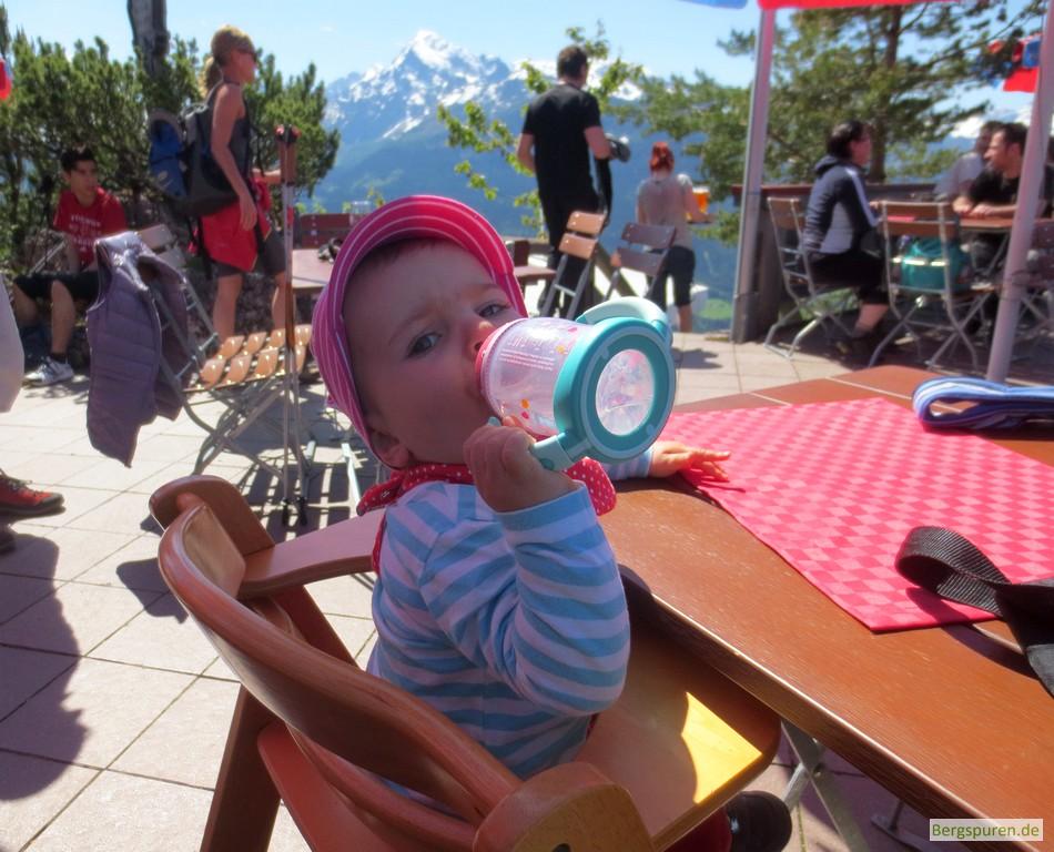 Kleinkind trinkt auf Terrasse der Berggaststätte Kneifelspitze