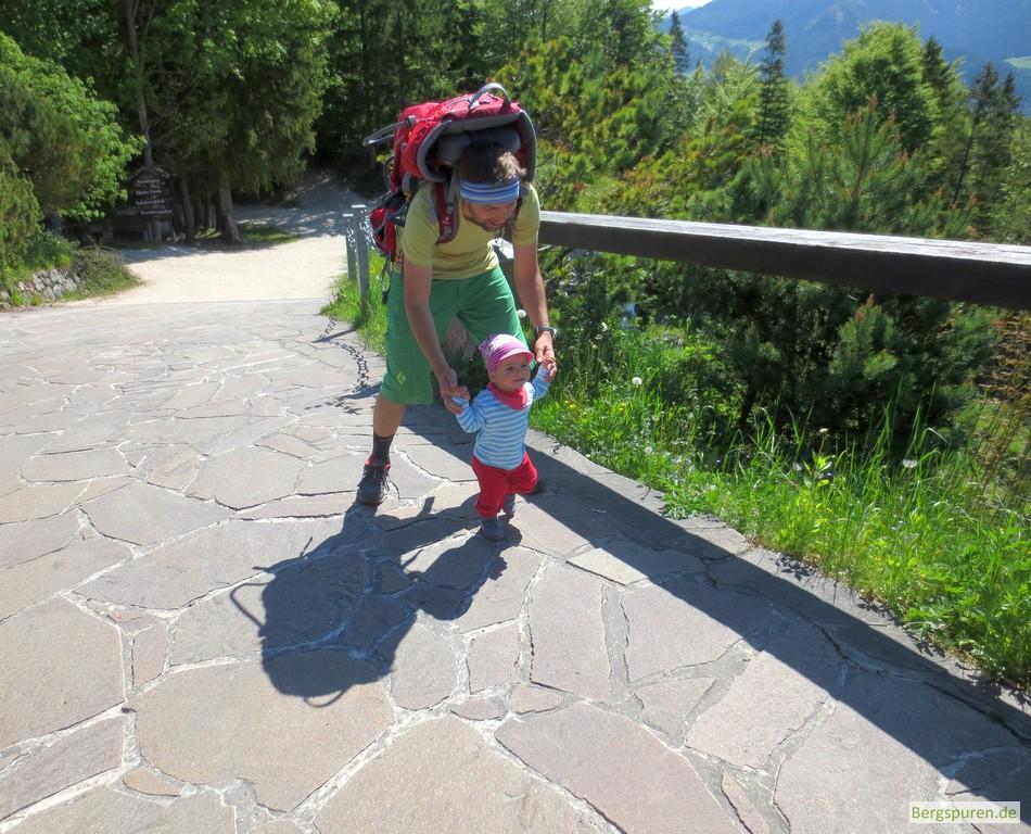 Kleinkind wird an den Händen auf den letzten Metern zur Berggaststätte Kneifelspitze geführt.