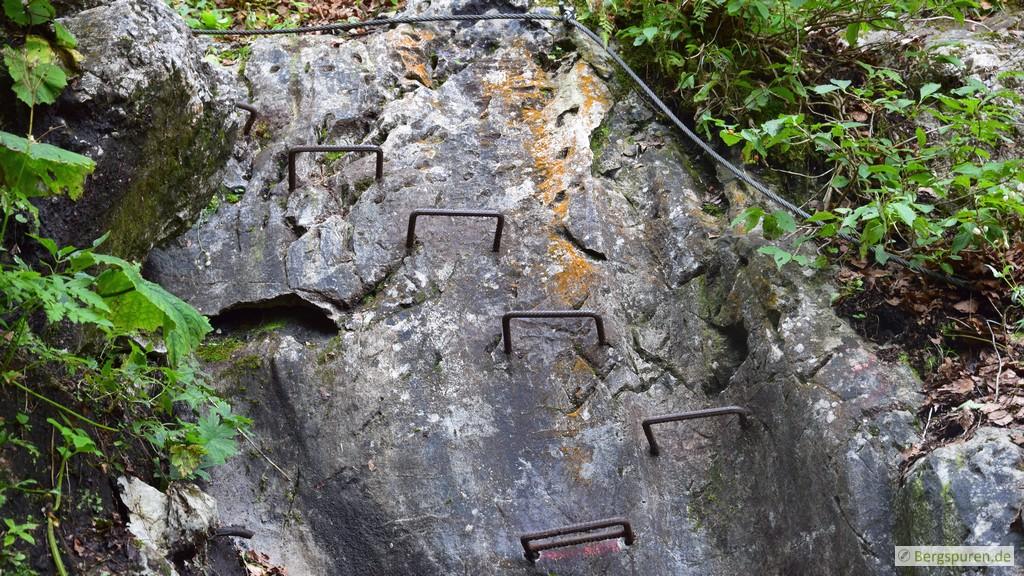 Kleine Felswand mit Eisentritten und Stahlseil